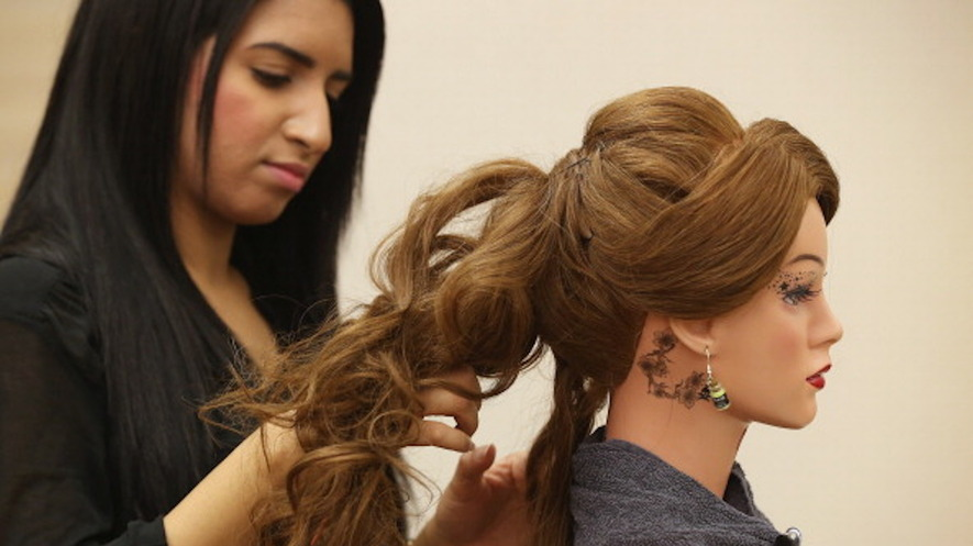 Top Hair Stylist Trainee Fatima Hussein Practices On A Mannequin At The Cut And Color