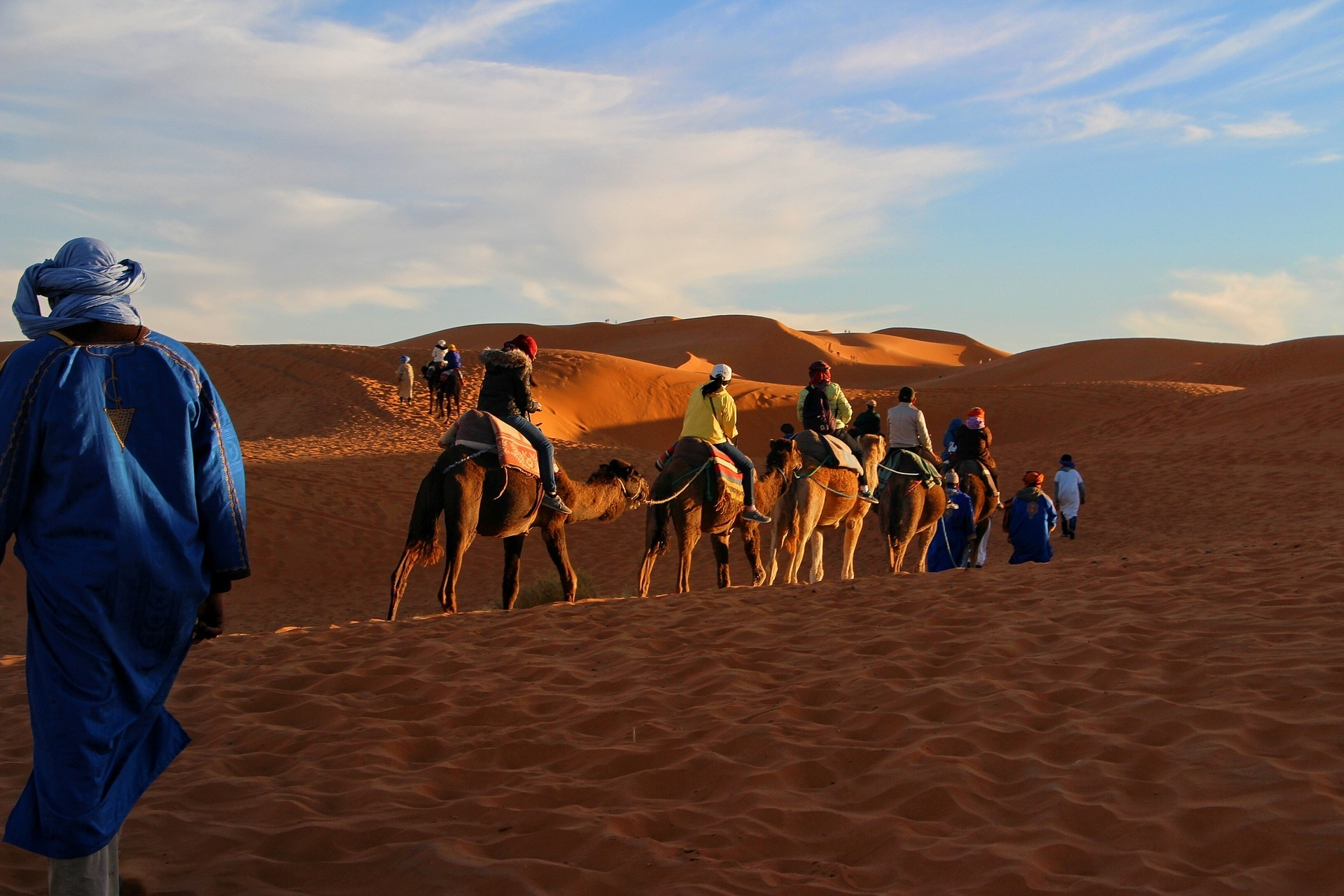 A caravan of travelers makes its way across the Sahara Desert, as people  have done